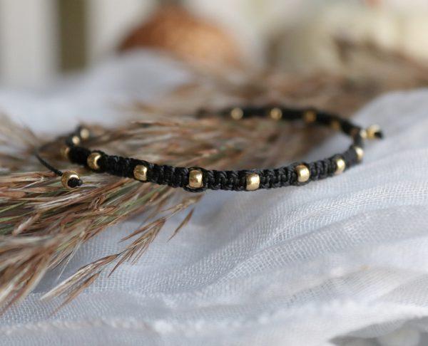 czarna bransoletka ze złotymi kuleczkami, wyplatany rzemyk na nadgarstek